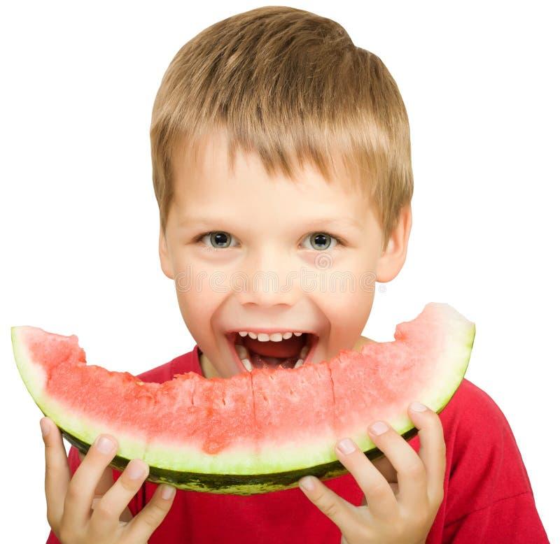 Junge, der ein Stück der Wassermelone isst stockfotos