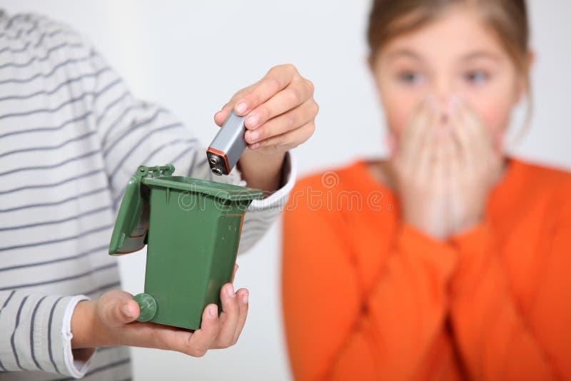 Junge, der eine Batterie in Behälter einsetzt stockfotos