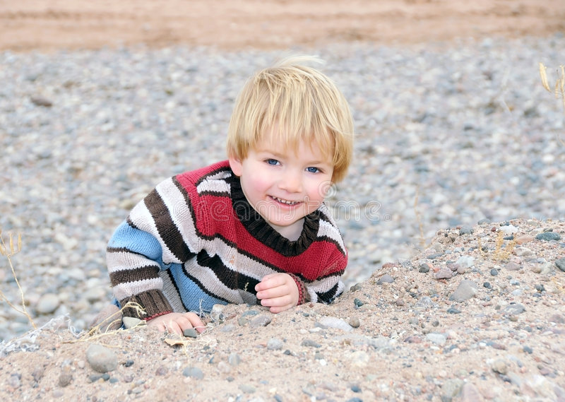Junge, der eine felsige Leiste steigt lizenzfreies stockfoto