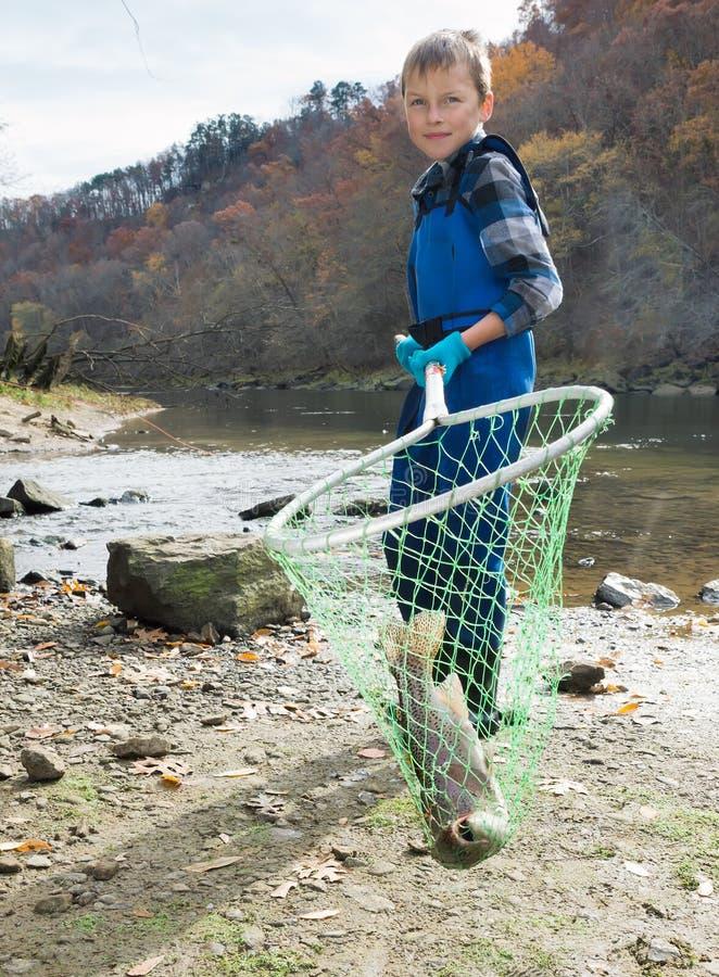 Junge, der eine frisch gefangene Forelle des Keschers hält lizenzfreies stockbild