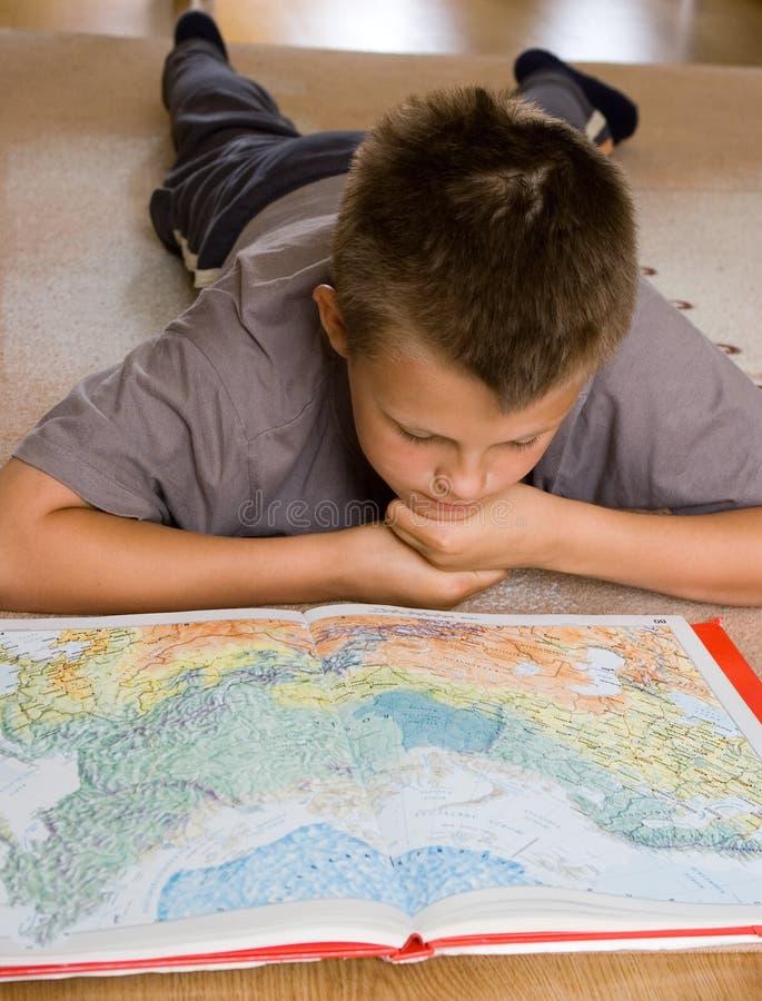 Junge, der eine Karte studiert lizenzfreie stockfotografie