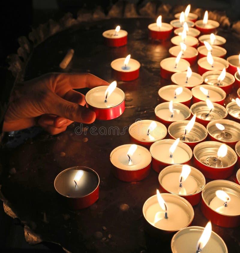 Junge, der eine Kerze setzt und ein Gebet für sein Schulergebnis vorträgt lizenzfreie stockbilder