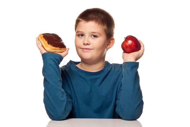 Junge, der an eine Nahrungsmittelwahl denkt stockbild