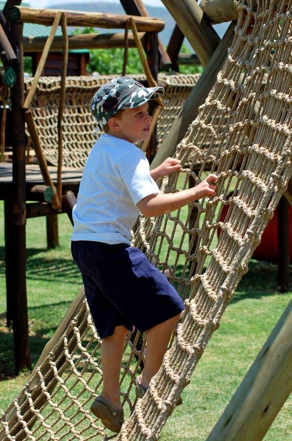 Junge, der eine Seilstrichleiter im Spielplatz steigt lizenzfreies stockfoto