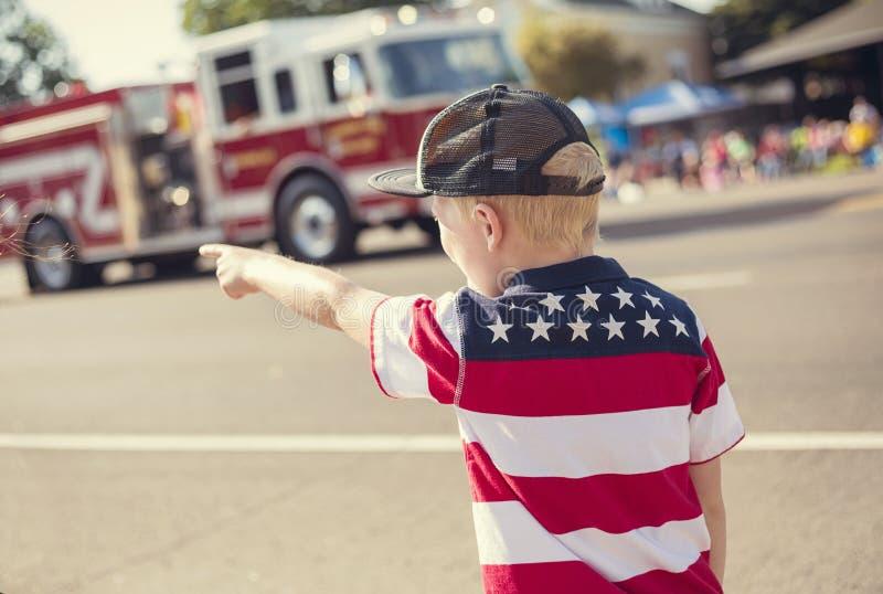 Junge, der eine Unabhängigkeitstag-Parade aufpasst stockfotografie