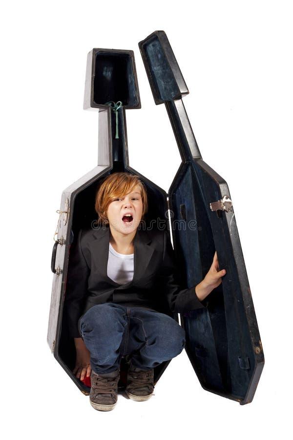 Junge, der in einem Cellokasten sich versteckt lizenzfreie stockbilder