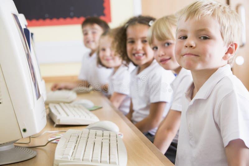 Junge, der an einem Computer an der Primärschule arbeitet stockbilder