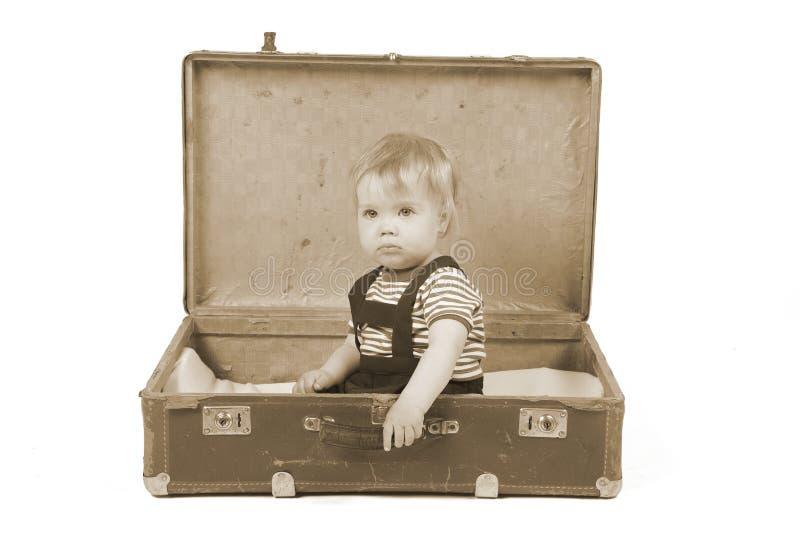 Junge, der in einem Koffer sitzt stockbild