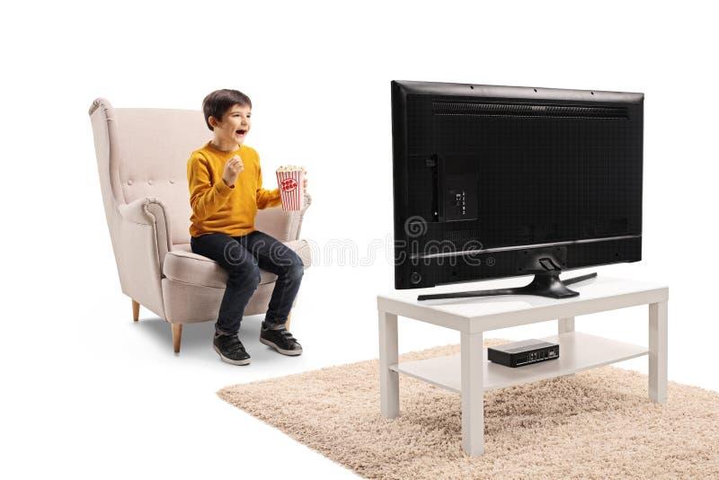 Junge, der in einem Lehnsessel mit Popcorn, aufpassendem Fernsehen und dem Lachen sitzt lizenzfreie stockbilder