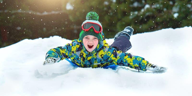 Junge, der in einem schneebedeckter Waldwinterspaß im Freien für Weihnachtsferien rodelt stockfoto