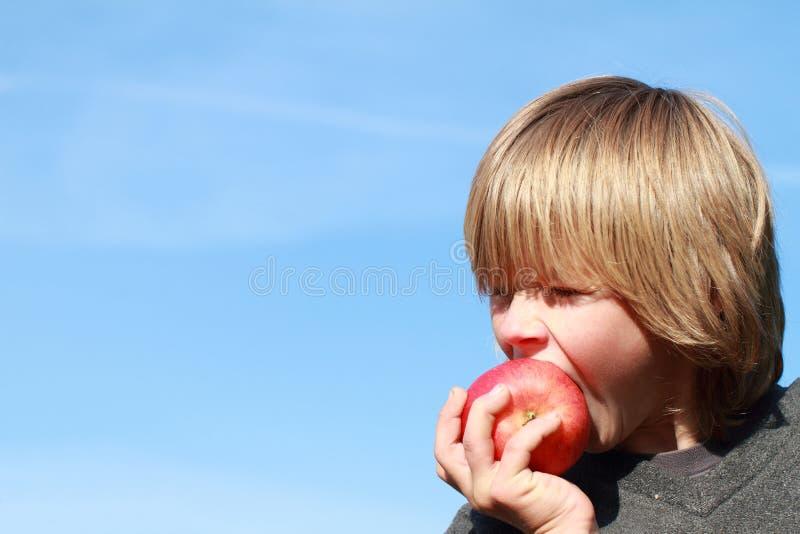 Junge, der einen Apfel isst lizenzfreie stockfotografie