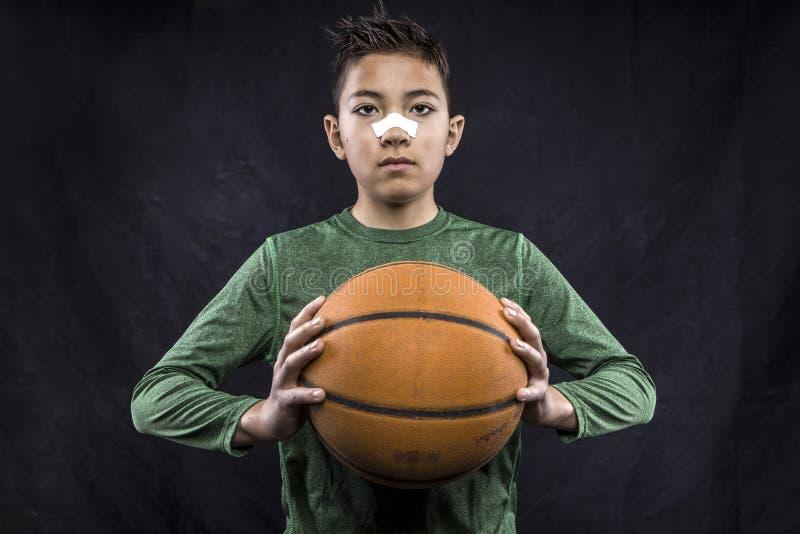 Junge, der einen Basketball anh?lt lizenzfreies stockbild