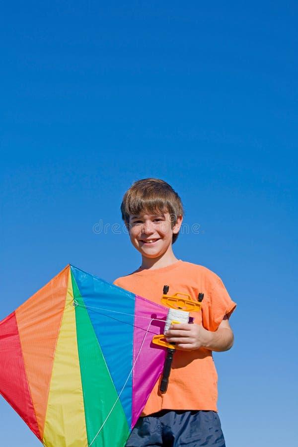 Junge, der einen Drachen fliegt lizenzfreies stockbild