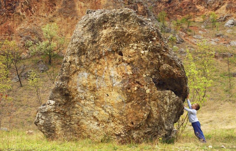 Junge, der einen Felsen unterstützt lizenzfreie stockbilder