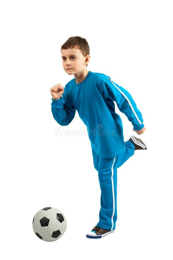 Junge, der einen Fußballstoß durchführt lizenzfreies stockfoto