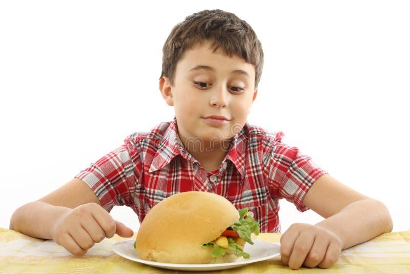 Junge, der einen großen Hamburger isst lizenzfreie stockfotografie