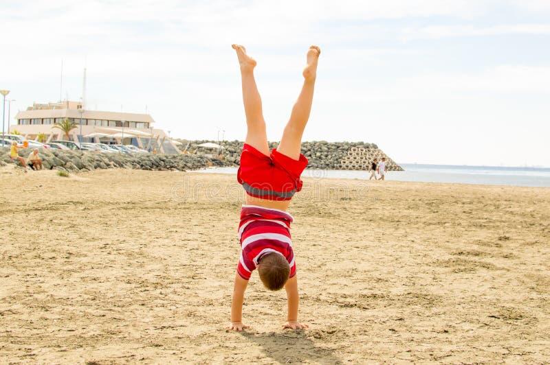 Junge, der einen Handstand tut stockfotografie