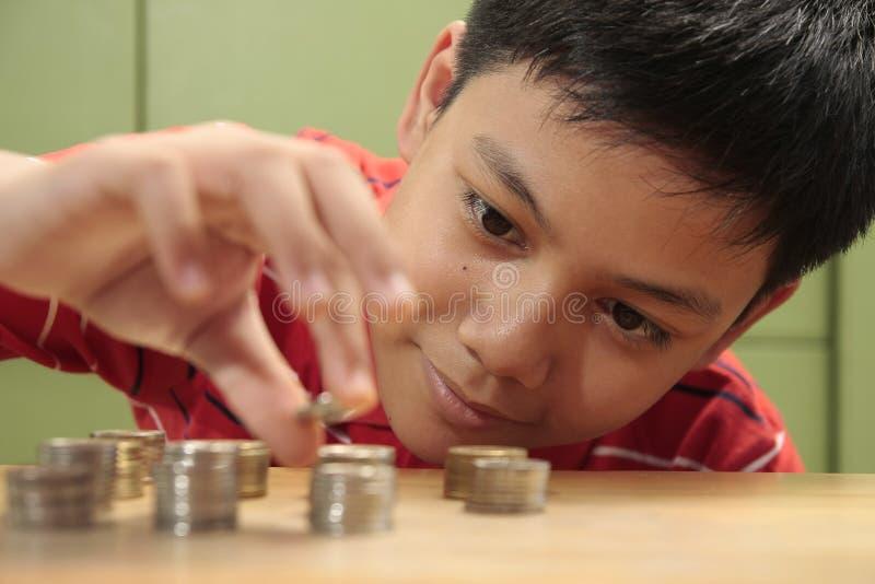 Junge, der einen Stapel der Münzen stapelt stockbild