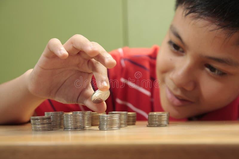 Junge, der einen Stapel der Münzen stapelt lizenzfreie stockbilder