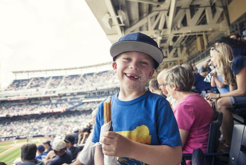 Junge, der einen Tag ein Spiel des professionellen Baseballs aufpassend genießt lizenzfreie stockfotos