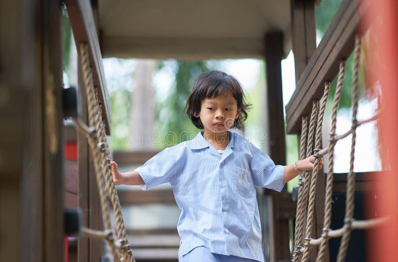 Junge in der einheitlichen Schule, die im Spielplatz spielt lizenzfreie stockfotografie