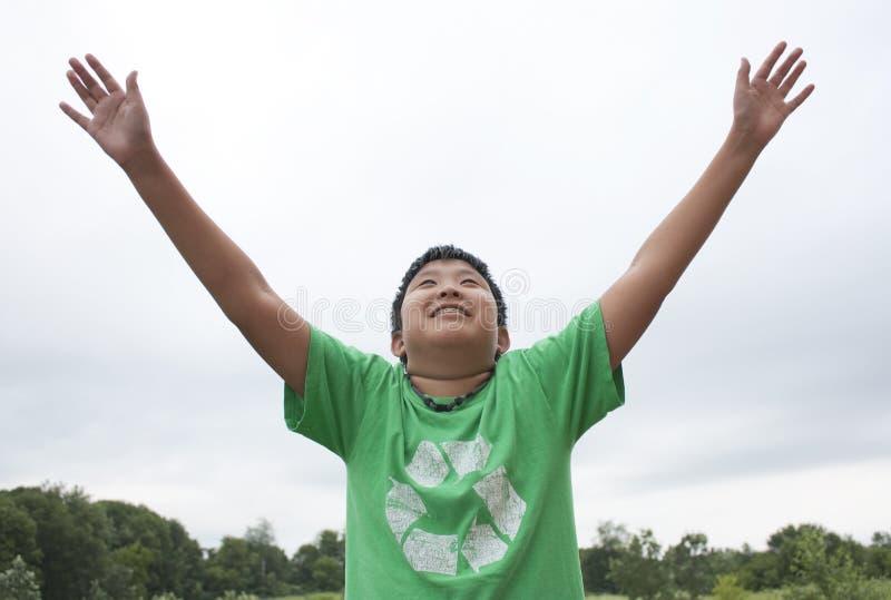 Junge, der für die Himmel erreicht stockfotografie