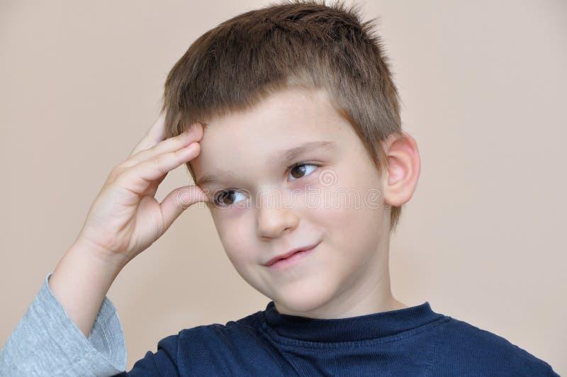 Junge, der Finger auf Kopf denkt und hält lizenzfreies stockfoto