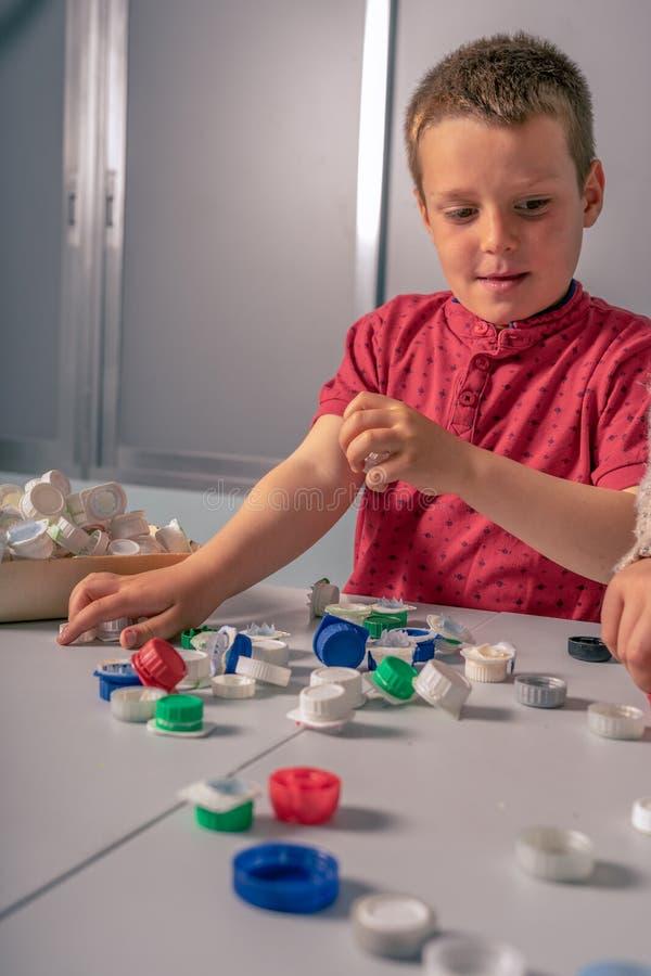Junge, der Flaschen und Plastikkappen, lustige Haltung aufbereitet stockfotografie