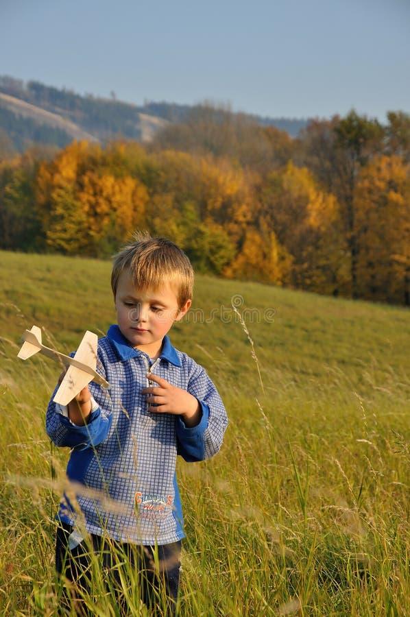 Junge, der Flugzeugbaumuster betrachtet lizenzfreie stockbilder
