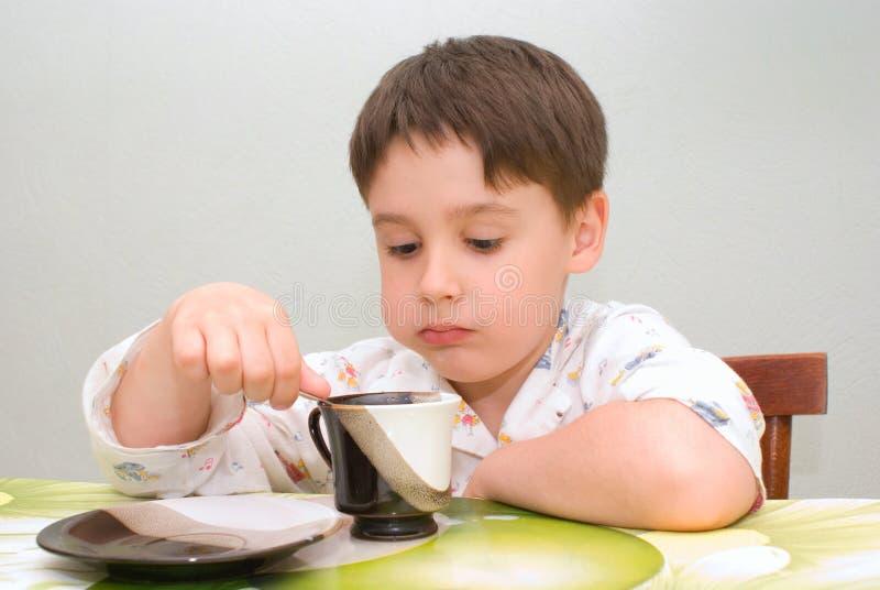Junge, der Fuß am Tisch isst lizenzfreie stockbilder