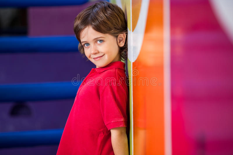 Junge, der gegen Wand im Kindergarten steht lizenzfreie stockfotografie