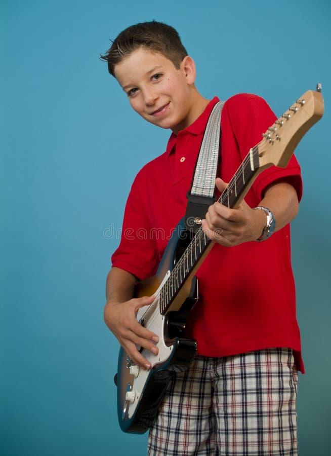 Junge, der Gitarre spielt lizenzfreie stockfotografie