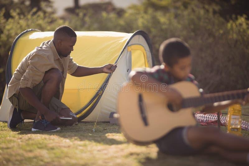 Junge, der Gitarre während Vater gründet ein Zelt im Park spielt lizenzfreies stockbild