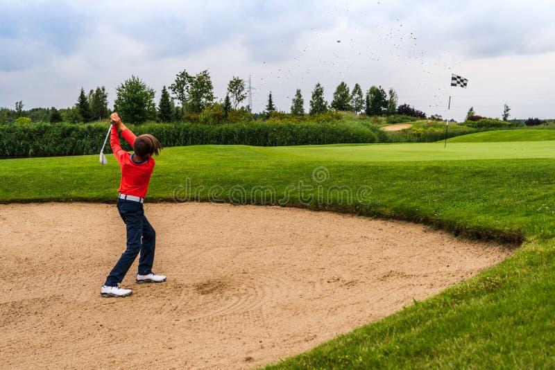 Junge, der Golf spielt stockfotos