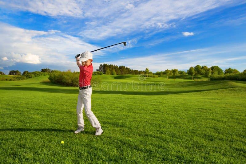 Junge, der Golf spielt stockfoto