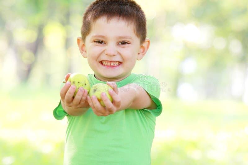 Junge, der grüne Äpfel gibt lizenzfreie stockfotos