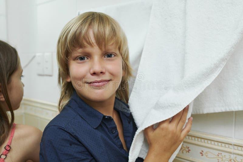 Junge, der Hände mit Tuch abwischt stockfotografie