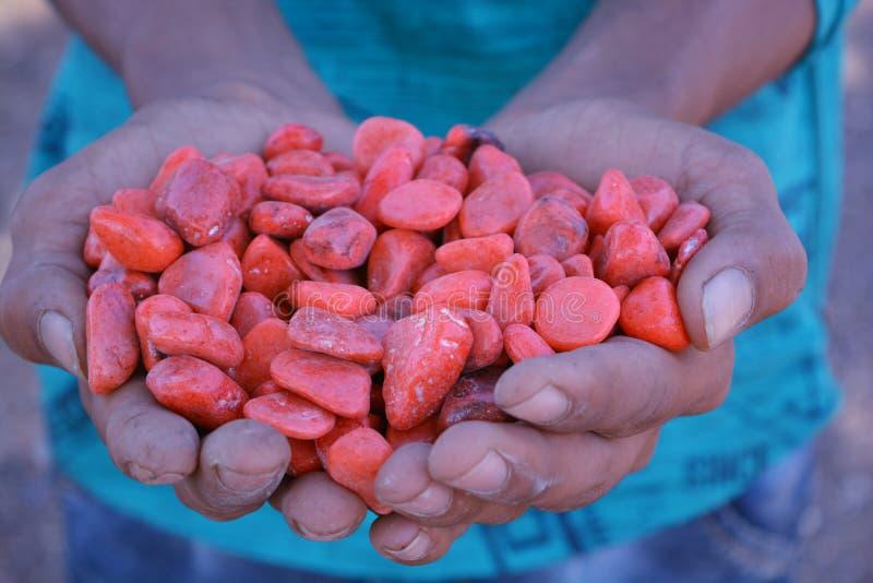 Junge, der in der Hand schöne bunte orange Steine hält lizenzfreies stockbild