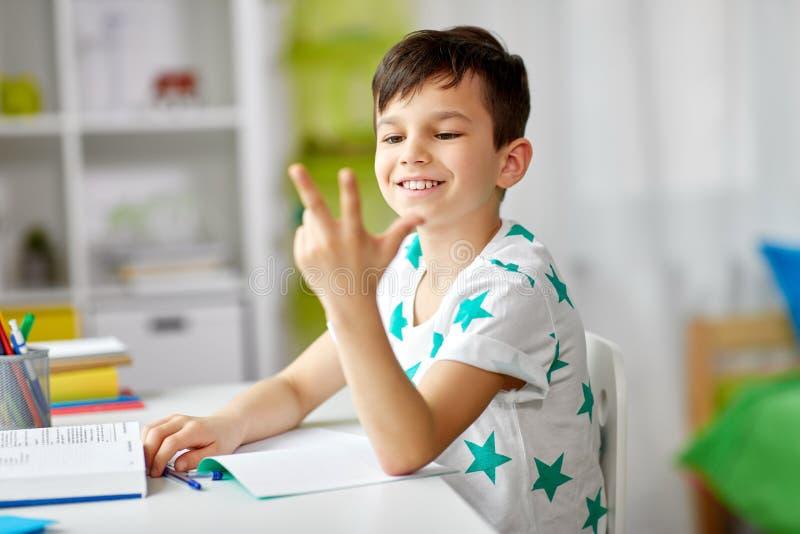 Junge, der Hausarbeit tut und unter Verwendung der Finger zählt lizenzfreie stockbilder