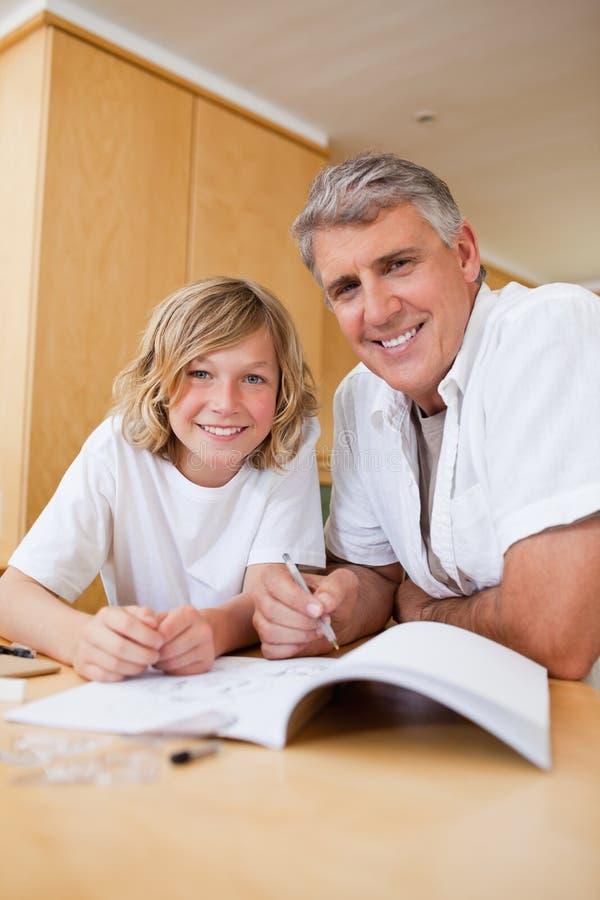 Junge, der Hilfe bei der Hausarbeit vom Vater erhält stockfotos