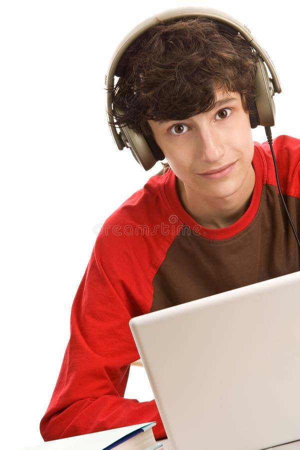 Junge, der hinter Schreibtisch sitzt stockfoto