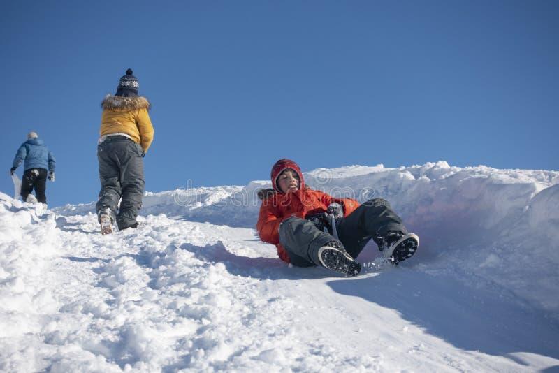 Junge, der hinunter einen Hügel im Schnee im Winter schiebt stockbild