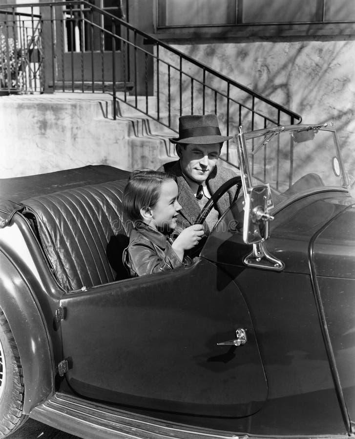 Junge, der im Fahrersitz des Autos mit seinem Vater sitzt (alle dargestellten Personen sind nicht längeres lebendes und kein Zust lizenzfreies stockfoto