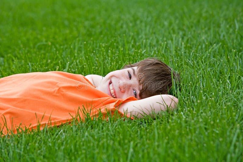 Junge, der im Gras liegt stockfotos