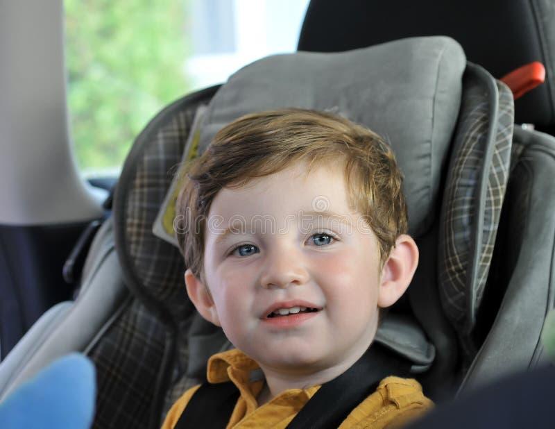 Junge, der im Kindautositz sitzt lizenzfreie stockfotos