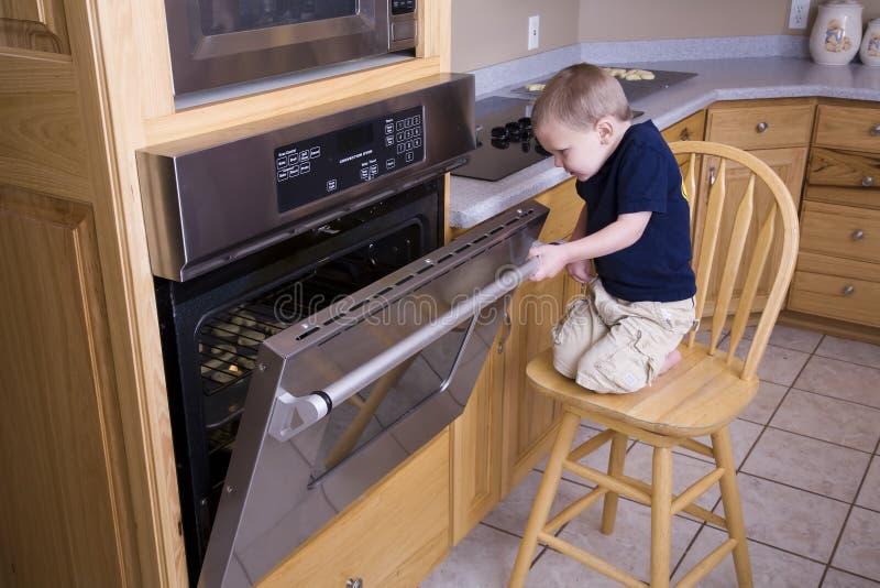 Junge, der im Ofen schaut stockbild