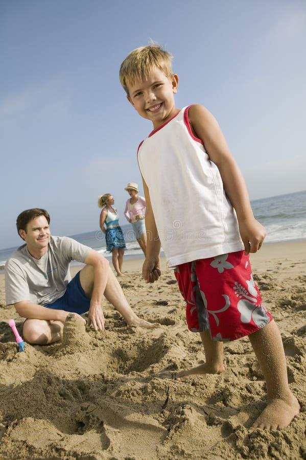 Junge, der im Sand mit Familie am Strand spielt stockbilder