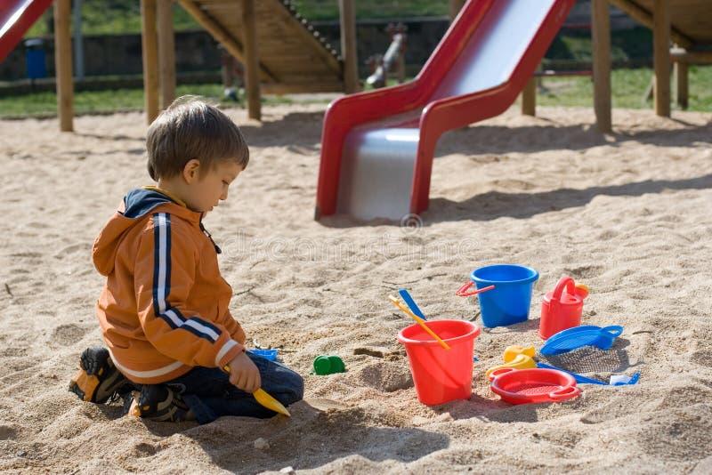 Junge, der im Sandkasten spielt stockfotografie