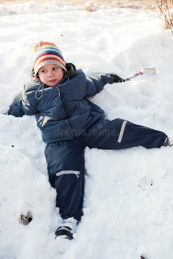 Junge, der im Schnee sich entspannt lizenzfreie stockfotos