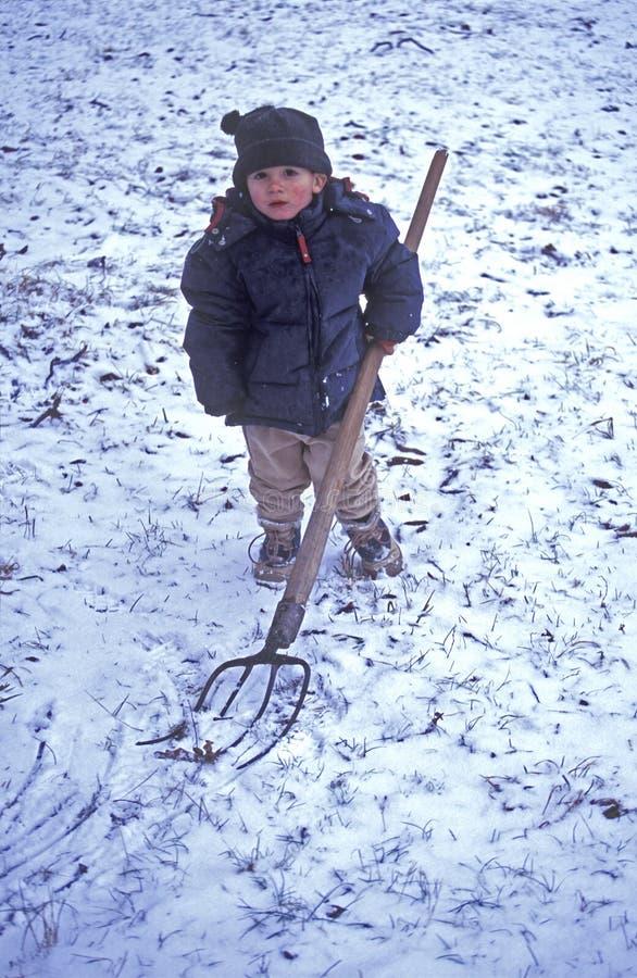 Junge, der im Schnee spielt stockbild